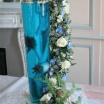 Une élégante guirlande de fleurs fraîches descend le long du vase en verre rempli d'eau colorée.
