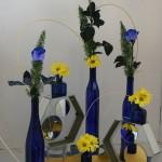 Jeu de bouteilles bleues, garnies de roses bleues et de chrysanthèmes jaunes, reliées par du rotin.