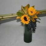 Un fagot de tiges, installé sur un vase haut et étroit, est décoré de fleurs de saison et de raisins.