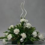 Branches de buis pailleté et oeillets blancs, boules de Noël et grandes bougies spirales.