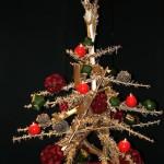 Reconstitué en morceaux de grande berce, sapin décoré de boules de roses, baies et bougies-boules.
