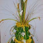 L'explosion d'herbes fines et d'arums blancs sort d'une fontaine en mimosas et feuilles travaillées.