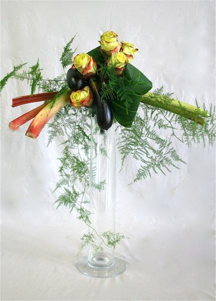 Sur un tube en verre, roses, aubergines et rhubarbe, sont accompagnées de feuilles de cordyline.