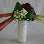 Décor de jardin sur un cylindre blanc avec rhubarbe et oeillets de poète rouge à l'arrière du bouquet.