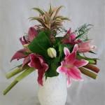 Des lys et un ananas  composent avec la rhubarbe un bouquet coloré de  fleurs et fruits.
