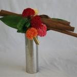 Des célosies multicolores et des feuilles d'aspidistra habillent un fagot d'écorces de cannelle.