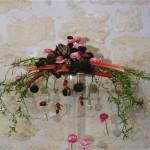 La rhubarbe est posée en fagot sur le vase, des petits radis dans les fioles, animent la compostion.