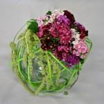 Les lanières de rotin sont agafées autour du vase qui contient les fleurs.
