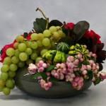 Symphorine rose, coloquintes vertes et grappe de raisin sur montage en grillage.