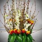 Composition de forsythias, tulipes et feuilles, agrémentée de quelques orchidées.