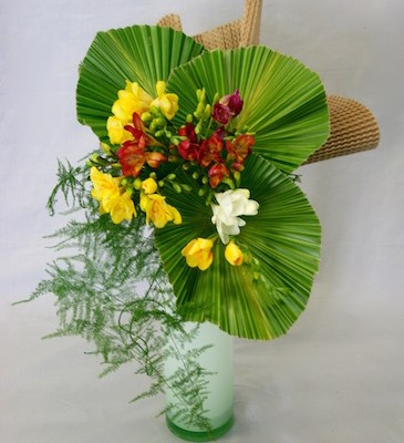 Les palmes mettent en valeur le simple bouquet de freesias.