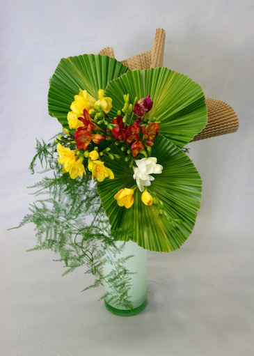 Les palmes mettent en valeur le simple bouquet de freesias.