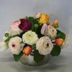 Tulipes et renoncules dans un arrangement rempli de fraîcheur printanière.