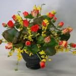 Branches de forsythias, roses en boutons complétés de feuilles de galax.