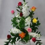 Bouquet triangulaire structuré de branches de ruscus et de giroflées, et animé de quelques roses multicolores.