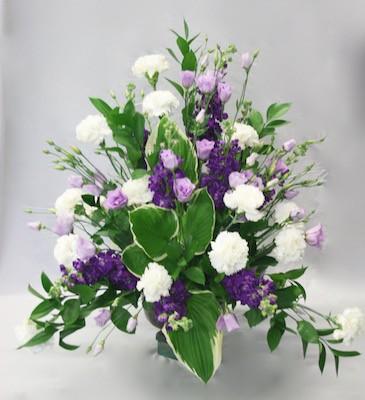Giroflées violettes, lisianthus mauves, oeillets blancs et hostas variegata pour le point focal du bouquet triangulaire.