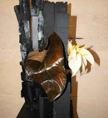 Callas et  feuilles d'anthurium chocolat sur montage bois et charbon de bois.