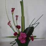 Le phormium, posé en croix est décoré de callas et roses roses.
