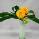 Le jeu de feuilles met en valeur les fleurs et le  raisin habille le vase haut.