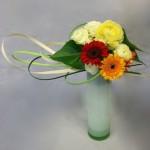 Bouquet rond multicolore  sur un haut vase cylindre en verre coloré.