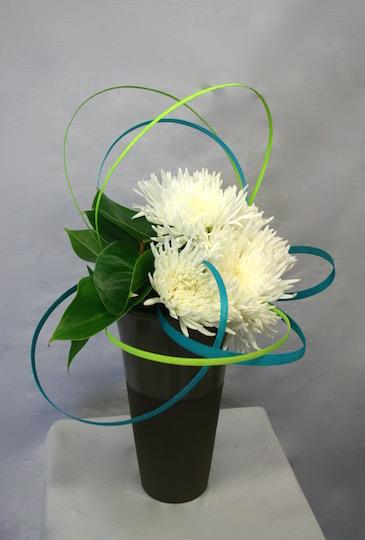 Les couleurs acidulées de l'accessoire égayent la masse blanche des fleurs.