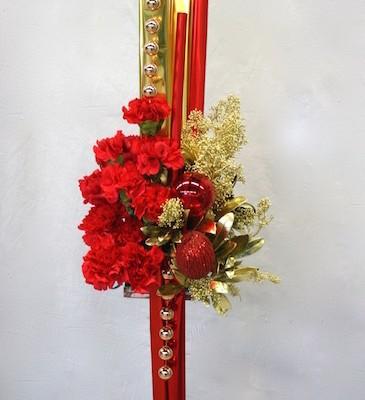 Des boules rouges, des chapelets dorés plus oeillets et  feuillage déclinent le thème.