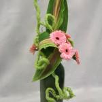 Quelques feuilles, fleurs et un accessoire, sont la base d'une composition équilibrée.