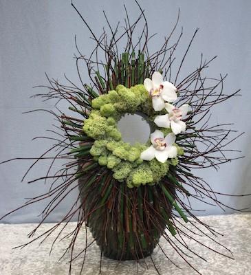 Une couronne végétale est posée sur un grand vase.