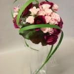 Deux variétés de roses habillées de longues feuilles de typhas.