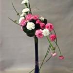 En rose et blanc,  renoncules et oeillets sur une élégante flûte bleue.
