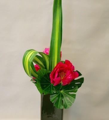 Composition minimaliste : ligne verticale, une grosse fleur et  jeu de feuilles.