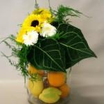 Un bocal en verre garni d'agrumes sert de vase, 2 grandes feuilles d'anthurium Clarinervium soulignent l'ensemble.