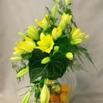 Gerbe de liliums jaune citron sur opulent vase en verre côtelé composent un bouquet de buffet estival.