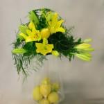 Les liliums jaunes sont posés sur un  haut photophore en verre transparent garni de citrons.