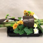 Les petits chrysanthèmes ainsi que les  feuilles de lierre forment un décor rustique.