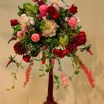 Bouquet rond rose et rouge sur un vase au col extravagant.