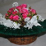 La composition de roses et de lierre est posée sur une corbeille en vannerie.
