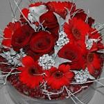 Roses et germinis rouges, sur une coupe en verre, éclairés de lierre et branches de myrtillier peint.
