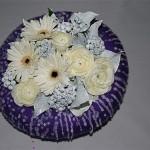 Renoncules et germinis rehaussés de baies de lierre peint . La couronne est en paille recouverte de laine à tricoter.