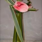 Anthuriums et phormiums dont les angulations s'inspirent des formes du haut contenant en verre.