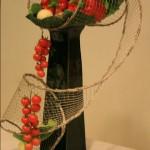 Décor Inspirations Florales pour un buffet : une volute de grillage sur un vase haut sert de corbeille.