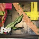 Grand tableau de tissages de végétaux colorés, feuilles de Marenta, orchidées et guirlande de diplocyclos.