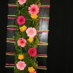 Décor aux couleurs acidulées sur fond noir : germinis roses et roses jaunes et hypericum vert.
