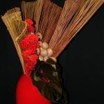 Grande volute réalisé en osiers, célosies rouges et feuilles d'anthurium.