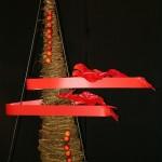 Sapin stylisé, petites pommes et lignes de plastique rouge soulignées d'anthuriums.