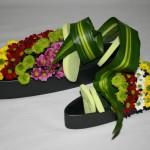 Travail en duo avec deux contenants allongés en céramique noire. Les petits chrysanthèmes santini sont travaillés en lignes de couleurs. Une feuille de Dracaena massangeana fait le lien entre les deux vases.