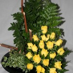 Fougères, Ficus pumila et gerbe de roses jaunes dans une sobre coupe en plastique noir.