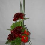 Pivoines, poivrons et feuillages pour une composition sur vase moderne.
