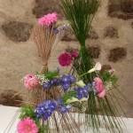 Coppet,  fleurs de jardin sur fagots de mikados,roses, delphiniums, arums.
