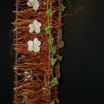 Colonne travaillée en saule tortueux tressé, orchidées et lianes de Diplocyclos.